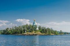 H?rlig sikt fr?n vattnet till ?n med den ortodoxa kyrkan St Nicholas Skete av den Valaam kloster Kyrka av St royaltyfri fotografi