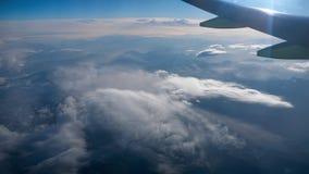 Härlig sikt till och med flygplanfönster, flygplanflyg ovanför berg och moln arkivfilmer
