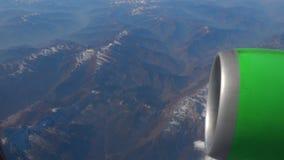 Härlig sikt till och med flygplanfönster, flygplanflyg ovanför molnen och berg arkivfilmer
