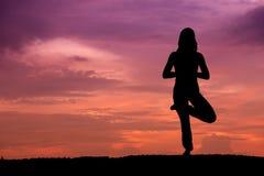 härlig silhouettekvinnayoga arkivbilder