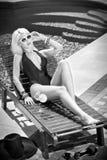 Härlig sinnlig blondin med trendig solglasögon som kopplar av på simbassängen med en fruktsaft Attraktiv lång ganska hårkvinna Royaltyfri Fotografi