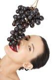 Härlig sinnlig brunett som äter druvor Arkivfoton