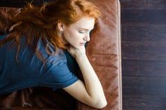 Härlig sinnlig kvinna som sover på den bruna lädersoffan Arkivfoto
