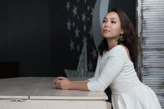 Härlig sinnlig och sexig asiatisk flicka i ett vitt klänninganseende nära pianot arkivbilder