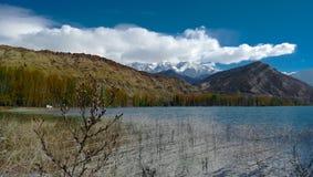 Härlig sjö med berg Arkivfoto