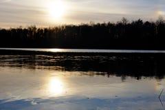 Härlig sjö och skog under solnedgång arkivbild