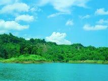 Härlig sjö som täckas av gröna kullar Arkivfoto