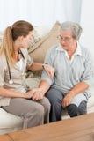 Härlig sjuksköterska som tar pulsen av henne som är patient Royaltyfri Foto