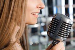 Härlig sjungande flicka Skönhetkvinna med mikrofonen Glamourmodell Singer Karaokesång arkivfoto
