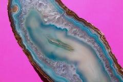 Härlig skiva av Aqua Blue Crystal Agate på en ljus rosa bakgrund arkivbild