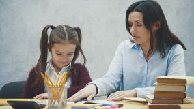 Härlig skolflicka som sitter på tabellen Gör läxa med hennes moder hemma stock video