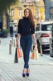 Härlig slank innegrej och stilfull kvinna i åtsittande jeans och Arkivfoton