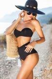 Härlig slank kvinna i stor hatt på stranden arkivfoto