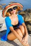 Härlig slank kvinna i stor hatt på stranden royaltyfri bild