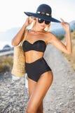 Härlig slank kvinna i stor hatt på stranden royaltyfri foto