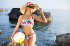 Härlig slank kvinna i stor hatt på stranden arkivbilder