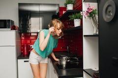 Härlig slank sexig flicka i kökmatlagningen fotografering för bildbyråer