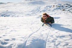 Härlig sledding för ung kvinna som är lycklig i snön Fotografering för Bildbyråer