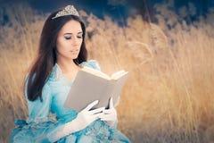 Härlig snödrottning som läser en bok royaltyfri bild