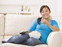 härlig soffa som äter popcornkvinnan arkivbilder