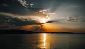 Härlig sol bak molnen och havet Arkivfoto