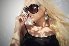 härlig solglasögonkvinna blond flicka för skönhet in nära väggen Sommar arkivfoto