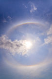 härlig solgloria med den runda regnbågen runt om solbehideblått Arkivbilder
