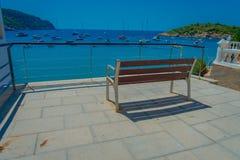 Härlig solig dag i den Sant almen, med en offentlig stol som tycker om sikten i Majorca, med folk som tycker om vattnet, in Royaltyfri Bild