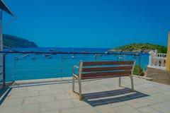 Härlig solig dag i den Sant almen, med en offentlig stol som tycker om sikten i Majorca, med folk som tycker om vattnet, in Arkivfoton