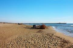 Härlig solig vinterdag på den sandiga stranden av Versilia på Forte dei Marmi Hamnplatsen på horisonten, lite blått hav och a arkivfoto