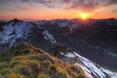 Härlig solnedgång över bergvapnen Arkivfoto