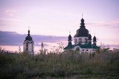 - Härlig solnedgång över den kristna kyrkan i förorterna av Kiev Arkivfoton