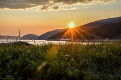 Härlig solnedgång över den Tadoussac fjärden och gräs- fält Arkivfoton