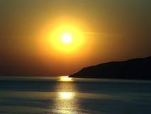 Härlig solnedgång över sihlouets för havskust av berg Arkivbild