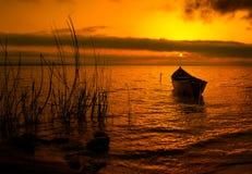 Härlig solnedgång över vatten och kontur av fiskebåten Arkivbilder