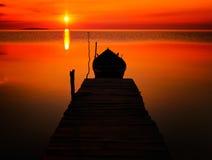 Härlig solnedgång över vatten och kontur av fiskebåten Royaltyfria Bilder