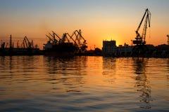 Härlig solnedgång bak en hamnstad Konturer av industriella kranar och byggnader med reflexioner i vattnet Arkivfoton