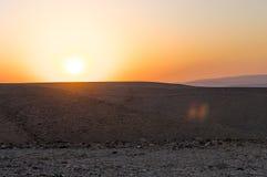 Härlig solnedgång i en stenig öken arkivfoton