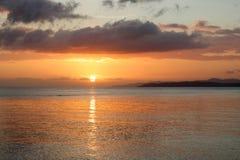 Härlig solnedgång i en tropisk ö med två personer som gör snor Arkivfoton