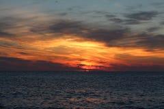Härlig solnedgång i havet på den sandiga stranden av badorten Royaltyfri Fotografi