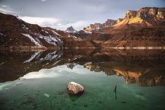 Härlig solnedgång i reflexionen av en bergsjö royaltyfri bild
