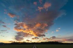 Härlig solnedgång med ängen och grusvägen Arkivbilder