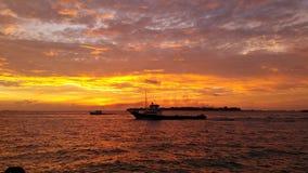 Härlig solnedgång med en snabb motorbåt på mitt Royaltyfri Foto