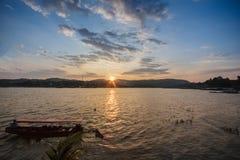 Härlig solnedgång med fartyget på sjön Arkivfoto