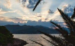 Härlig solnedgång med guld- strålar som bryter till och med moln på en ö arkivbilder