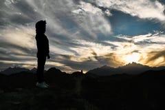 Härlig solnedgång med moln i bergen upptill av bergkonturen av en stående pojke royaltyfria bilder