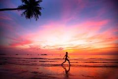 Härlig solnedgång med silhouettes av joggerflickor Arkivbild