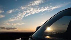 Härlig solnedgång och himmel med moln till och med vindrutan av bilen Royaltyfri Bild