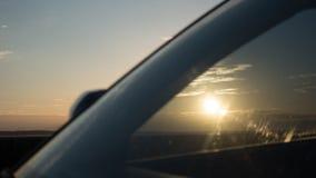 Härlig solnedgång och himmel med moln till och med vindrutan av bilen Arkivfoton