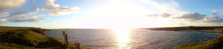 Härlig solnedgång och molnig himmel på den irländska kusten nära klipporna av Moher Arkivbild
